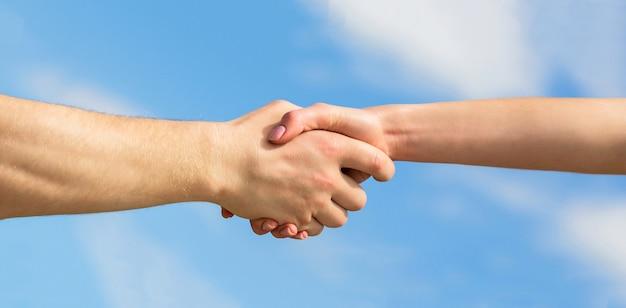Eine helfende hand geben. eine helfende hand leihen. solidarität, mitgefühl und nächstenliebe, rettung. hände von mann und frau auf blauem himmelshintergrund