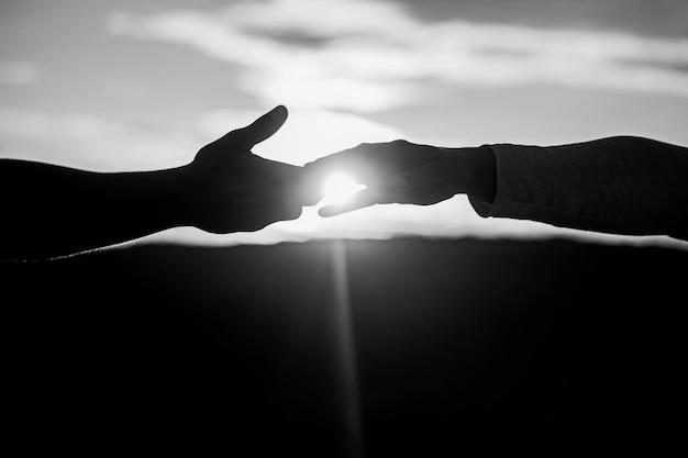 Eine helfende hand geben. rettung, helfende geste oder hände. silhouette mit zwei händen auf himmelshintergrund, verbindung oder hilfekonzept. schwarz und weiß.