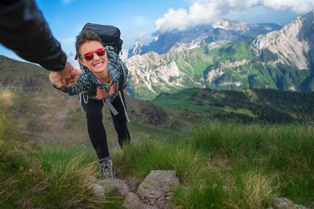 Eine helfende hand hilft einem mädchen in den bergen, sie bei der hand zu nehmen und zu ziehen