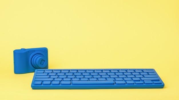 Eine hellblaue tastatur und eine hellblaue kamera auf einem gelben hintergrund. stilvolles zubehör für geschäftsreisende und freiberufler.