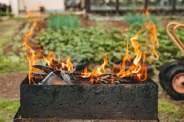 Eine helle flamme aus dem feuer. flammen über dem grill. holzstäbchen im feuer