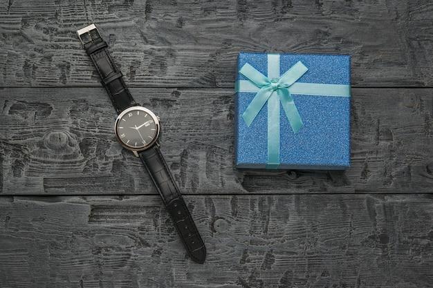 Eine herrenuhr mit zeigern und einer geschenkbox auf einem schwarzen holztisch. ein geschenk für einen mann.