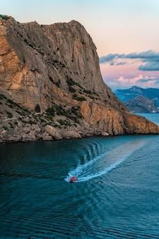 Eine herrliche landschaft bei sonnenuntergang vom kap kapchik auf der krim ein boot segelt auf dem schwarzen meer