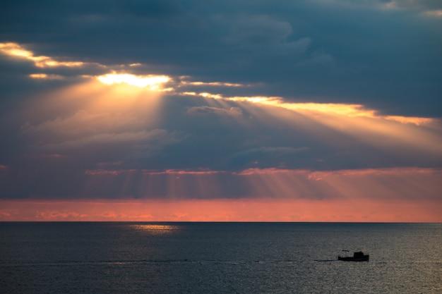Eine herrliche seelandschaft mit dramatischen wolken und sonnenlicht, ein boot, das im meer schwimmt