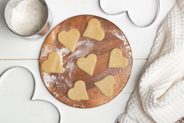 Eine herzförmige ausschnittform und ein teig schnitten kekse neben einem handtuch und holzlöffeln und einem becher zum sieben von mehl, flach liegend.