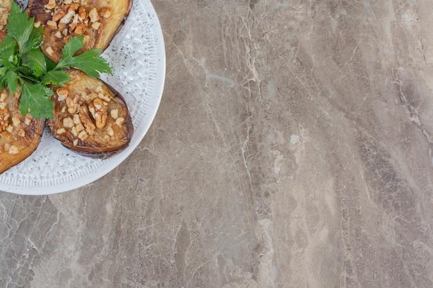 Eine herzhafte platte mit indischen auberginen, gebraten und gewürzt mit knoblauch, geschmückt mit petersilie auf marmor.