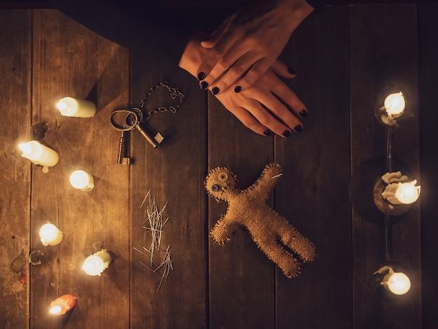 Eine hexe im dunkeln hält eine voodoo-stoffpuppe, umgeben von kerzen, flach liegend.