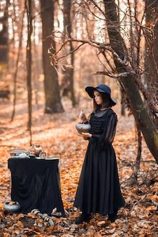 Eine hexe im herbstwald. eine frau in einem schwarzen langen kleid, die einen trank kocht, bereitet sich auf halloween vor