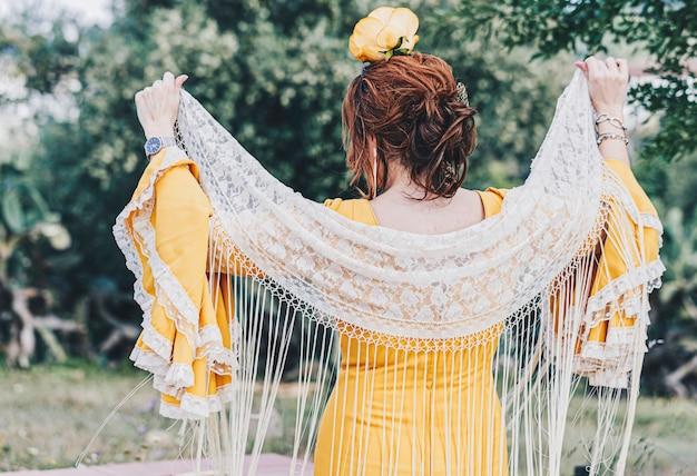 Eine hintere spanische frau, die eine gelbe traditionelle flamencoart-kleiderstellung trägt