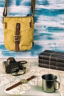 Eine hipster-tasche, einige bücher, eine armbanduhr und eine alte filmkamera.