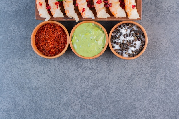 Eine hölzerne platte der köstlichen garnelen mit geschnittener kirschtomate und pfeffer auf einem steinhintergrund.