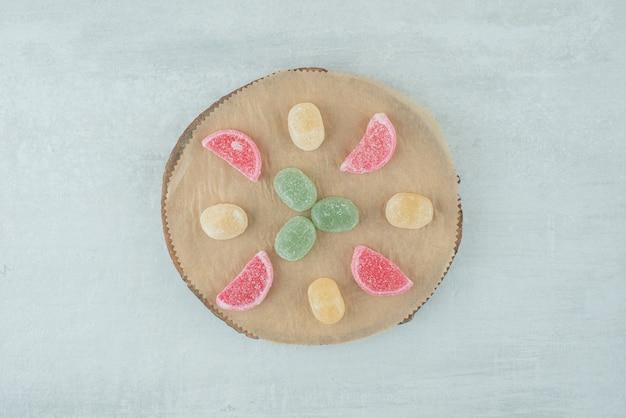 Eine hölzerne platte voller zuckermarmelade auf weißem hintergrund. hochwertiges foto