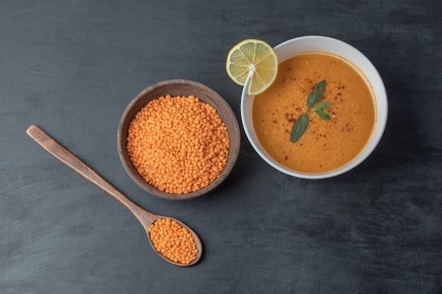 Eine hölzerne schüssel linsenbohnen mit suppe und zitronenscheibe.