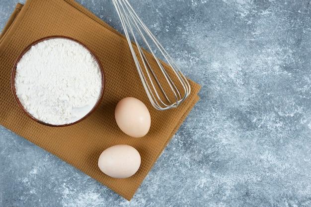 Eine hölzerne schüssel mehl mit zwei frischen hühnereiern und schneebesen.