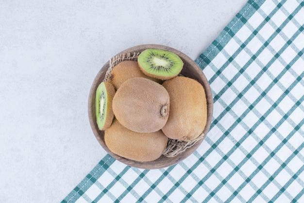 Eine hölzerne schüssel mit frischer kiwi auf weißem hintergrund. foto in hoher qualität