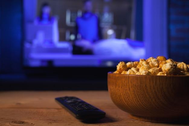 Eine hölzerne schüssel popcorn und fernbedienung.