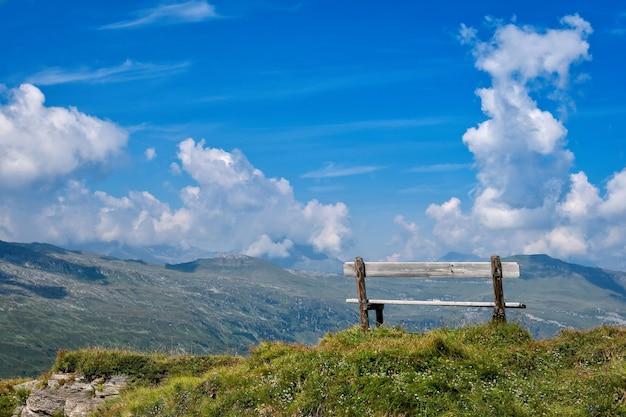 Eine holzbank auf dem gipfel der alpen, ein ort, an dem sich touristen entspannen und wunderschöne landschaften betrachten können.