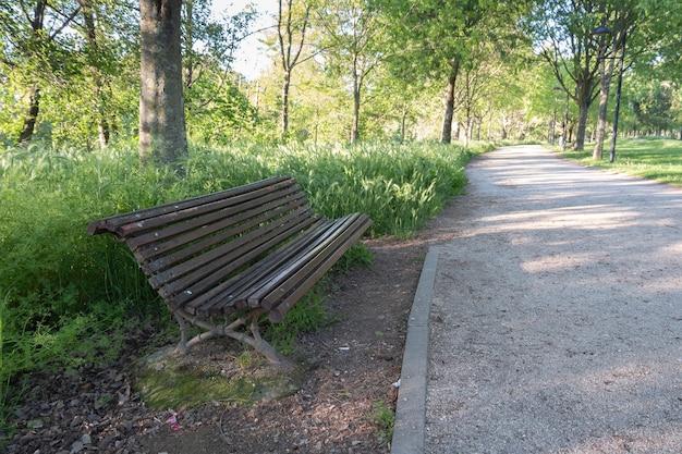 Eine holzbank lädt zum sitzen und ausruhen neben dem schotter- und schotterweg in einem öffentlichen park ein