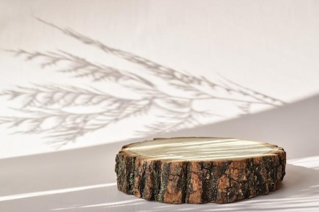 Eine holzbühne mit schatten zur präsentation umweltfreundlicher produkte. das podium besteht aus natürlichem material mit platz für text. minimalistische branding-szene.