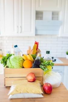 Eine holzkiste mit verschiedenen lebensmitteln, obst, gemüse, öl, wasser und zucker in der küche. sichere lieferung nach hause.