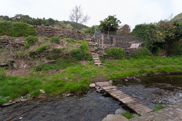 Eine holzplankenbrücke, um den fluss arrago zu überqueren und den bio-garten und den hühnerstall zu erreichen