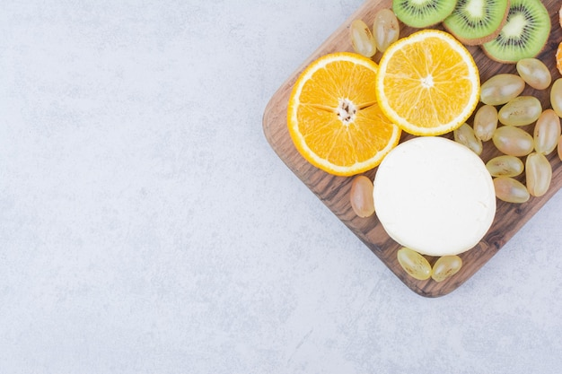 Eine holzplatte mit geschnittenem käse und früchten. foto in hoher qualität