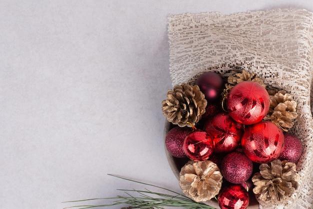 Eine holzplatte mit roten weihnachtskugeln und tannenzapfen auf sackleinen.
