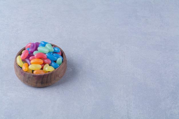 Eine holzschale mit bunten süßen jelly bean bonbons. foto in hoher qualität