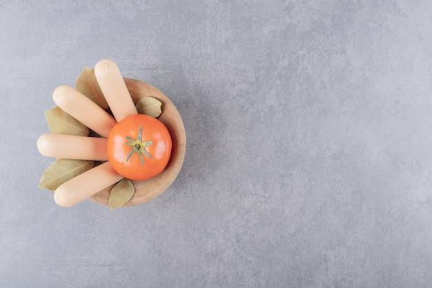 Eine holzschale mit gekochten würstchen mit roten tomaten und lorbeerblättern.