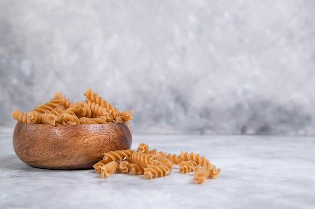 Eine holzschale mit italienischen ungekochten trockenen nudeln fusilli. hochwertiges foto