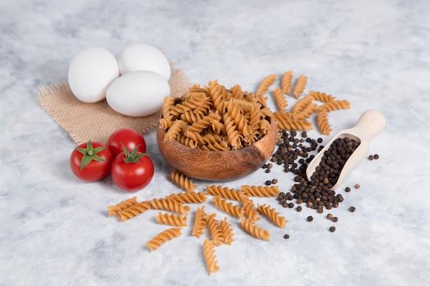 Eine holzschale mit italienischen ungekochten trockenen nudeln fusilli mit pfefferkörnern. hochwertiges foto