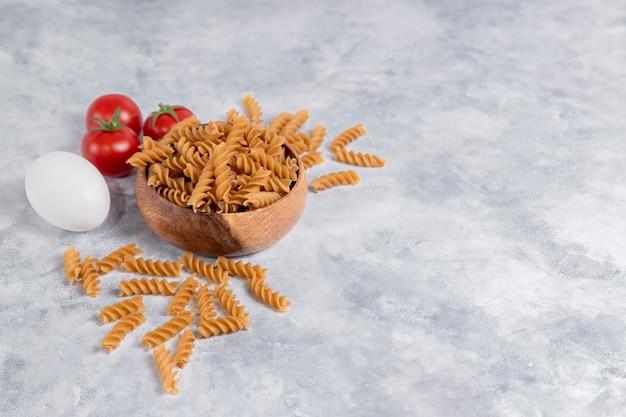 Eine holzschale mit italienischer ungekochter trockener pasta fusilli rigate mit tomaten. hochwertiges foto