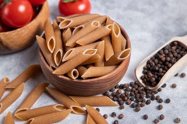 Eine holzschale mit italienischer ungekochter trockener pasta penne rigate mit tomaten und pfefferkörnern. hochwertiges foto