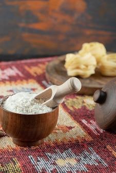 Eine holzschale mit mehl und holzbrett mit gerollten rohen nudeln