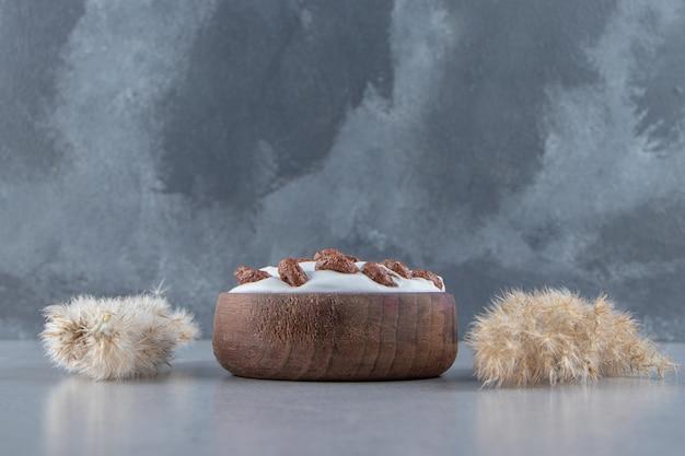 Eine holzschale mit sahne- und schokoladengetreide auf steinhintergrund. foto in hoher qualität