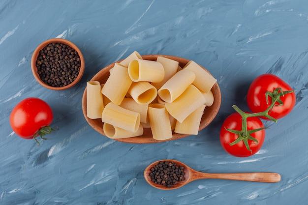 Eine holzschale mit trockenen rohen röhrennudeln mit frischen roten tomaten und gewürzen auf einem blauen tisch.