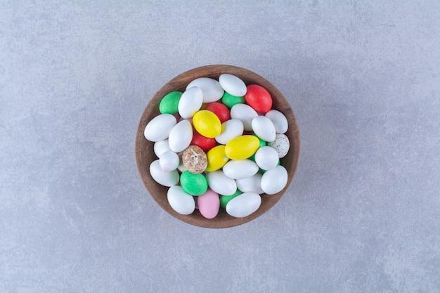 Eine holzschale voller bunter bohnenbonbons auf grauem hintergrund. foto in hoher qualität