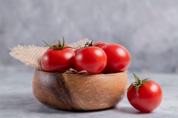 Eine holzschale voller frischer saftiger roter tomaten auf steintisch. hochwertiges foto