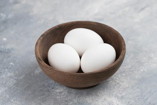 Eine holzschale voller frischer weißer hühnereier auf einem marmor.