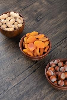 Eine holzschale voller getrockneter aprikosenfrüchte mit gesunden nüssen.