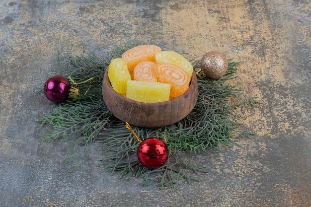 Eine holzschale voller orangen und gelber bonbons aus fruchtgelee. hochwertiges foto