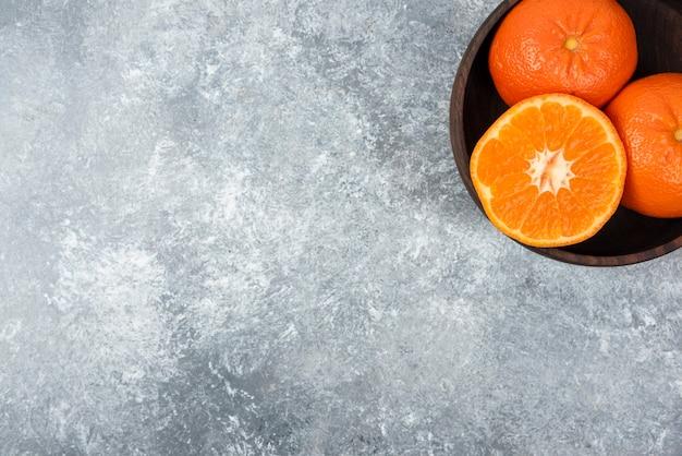 Eine holzschale voller saftiger orangenfrüchte auf steintisch.