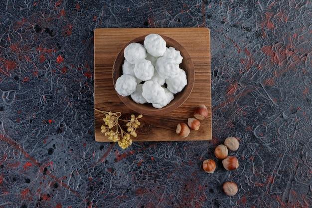 Eine holzschale voller süßer weißer bonbons mit gesunden nüssen auf einem dunklen tisch.