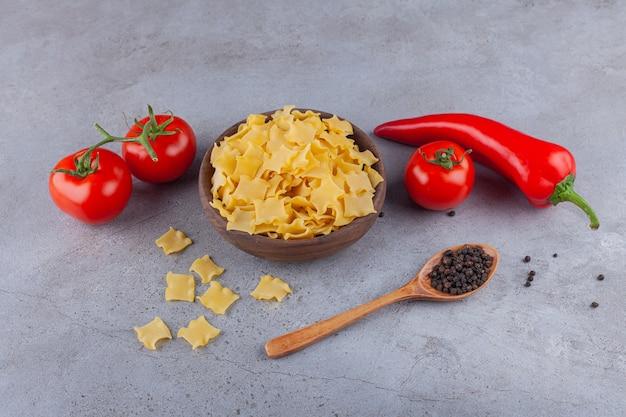 Eine holzschale voller ungekochter ravioli-nudeln mit roten frischen tomaten und chili-pfeffer.
