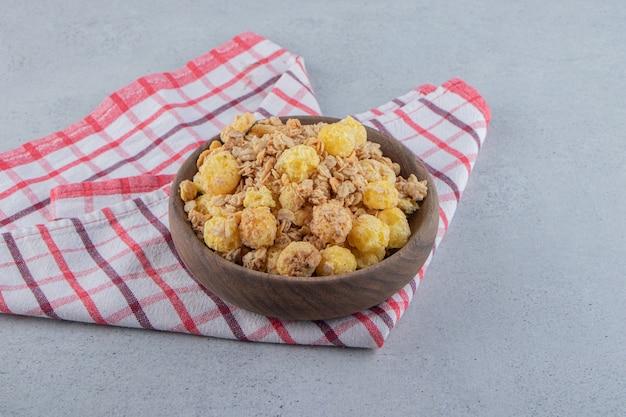 Eine holzschüssel mit leckeren gesunden cerealien auf einer tischdecke. foto in hoher qualität