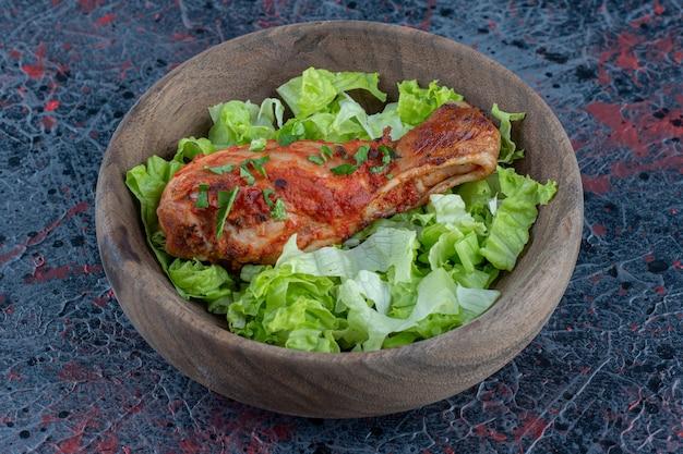 Eine holzschüssel mit salat und gebratenem hühnerkeulenfleisch