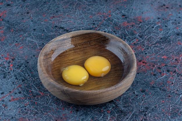 Eine holzschüssel mit zwei rohen hühnereiern.