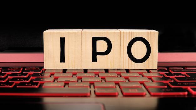 Eine holzstange mit einem ipo-wort auf der beleuchteten laptoptastatur
