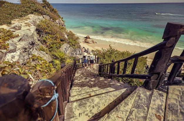 Eine holztreppe führt zum strand von tulum in mexiko hinab, damit touristen den höhenunterschied überwinden können, um zum strand zu gelangen.