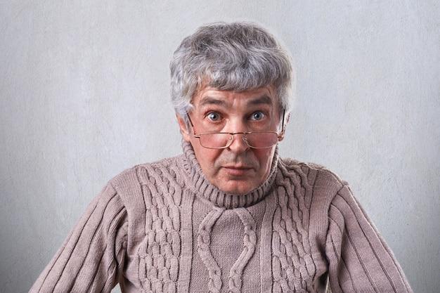 Eine horizontale mittlere nahaufnahme eines älteren mannes mit den schönen augen des grauen haares, die falten auf dem gesicht tragen, das brillen posiert